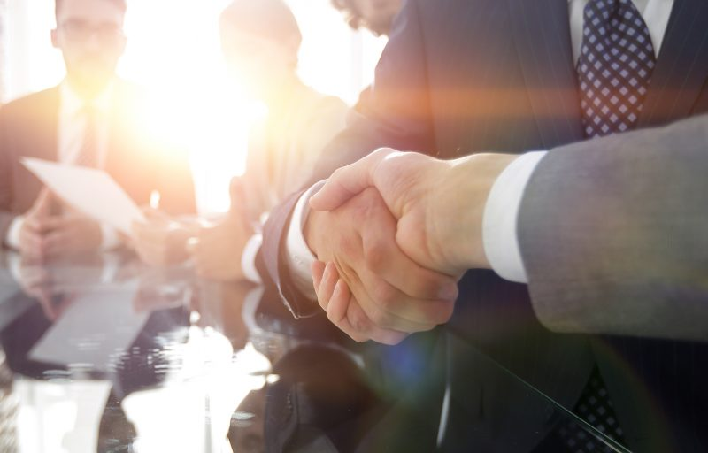 background image of handshake of business partners in conference room